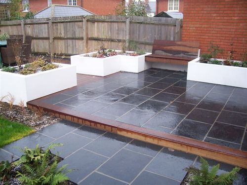 modern gardens witham view of step up to small patio in truslate